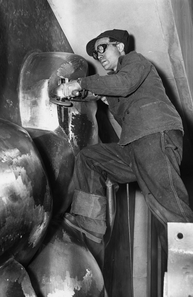 Black and white photo of wearing goggles sculpting metal works
